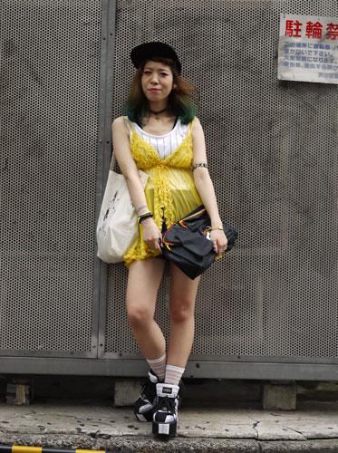 写真:ツートーンのヘアスタイルに、タンクトップにランジェリー調のトップスを重ねて。足元はお約束の厚底。