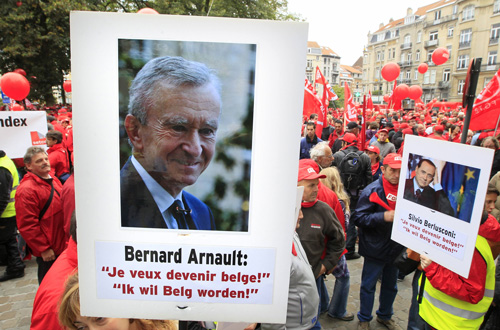 写真:LVMHグループの最高経営責任者(CEO)・ベルナール・アルノー氏のベルギー国籍取得申請に対して抗議する人々(ロイター)