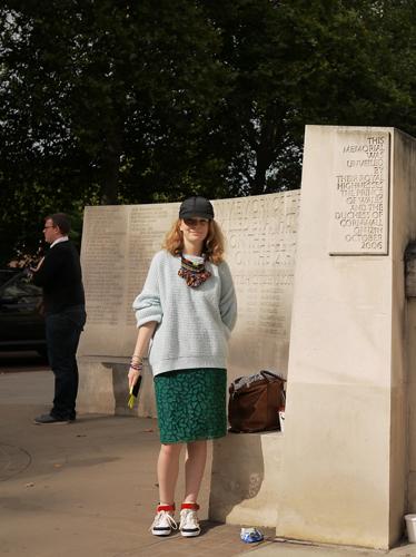 写真:グリーンのタイトスカートにはビックサイズのニットを合わせて上級者スタイル。キャップやスニーカーでストリートテイストを取り入れて。
