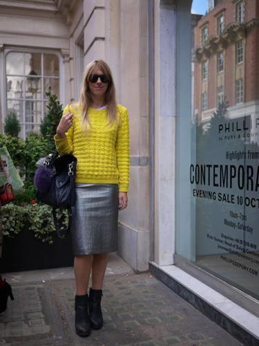 写真:鮮やかなイエローのニットの彼女。シルバーのタイトスカートと合わせてシックに。マーガレットハウエルのショー会場で。