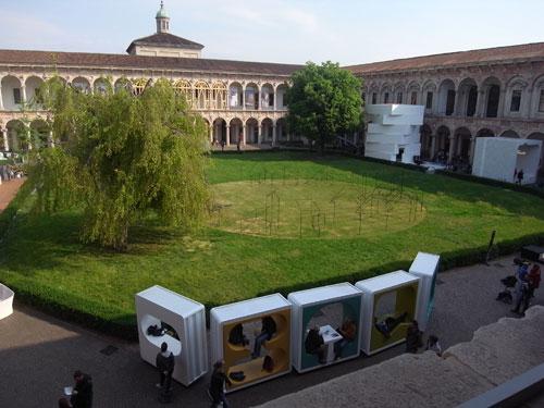 写真:ミラノ大学のインテルニ展。構内の回廊や庭には有名デザイナーによる作品が数多く展示されている。手前下はアート・コンテナ社製移動野外家具。