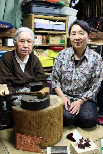 写真:「錺(かざり)金具」の技術で名刺入れを作る塩澤カネさん(左)、政子さん親子