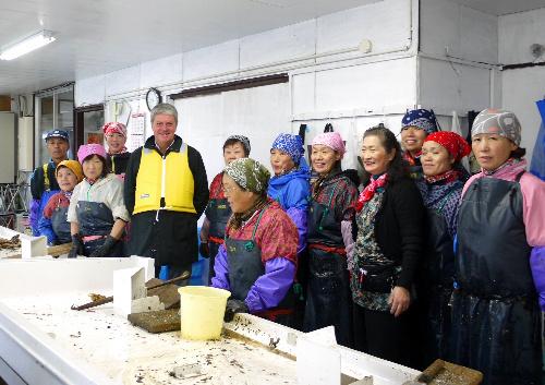 写真:再建した加工場で従業員とルイ・ヴィトンのイヴ・カルセル本社会長(左から5人目)
