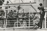 神戸に来日し、船上で花束を掲げて歓声にこたえるチャールズ・チャップリン。右隣は兄のシドニー氏。左隣は高野秘書。着物の女性は女優の夏川静江=1932年5月14日