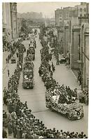 第2回「みなとの祭」の国際大行進。花自動車が神戸港の前を進む。後方に貨物船や倉庫群が見える=1934年11月7日、日本郵船神戸支店から撮影