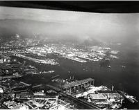 1955年に撮影された神戸港。手前は川崎重工神戸工場のドック。後方は六甲山=1955年11月27日、神戸市葺合区東川崎町(現・中央区)、朝日新聞社機から