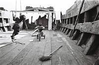 子どもたちはどこでも遊び場にする。せまいはしけの甲板でブランコをこいだり、三輪車で走り回る=1964年