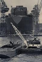 進水式を前に、進水路のしゅんせつ作業がはじまった。海はヘドロなどがたまって深さ12メートルしかないのに船の満水喫水は17メートル。進水の時つかえぬように15メートルまでしゅんせつする。後方はノルウェー