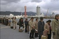 地震から1カ月、天保山行きの高速艇に乗り込むため列をつくっていた乗客たちが正午の汽笛に合わせて黙祷した=1995年2月17日
