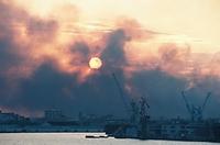 神戸港から西側をのぞむと地震によって発生した火災の黒煙の向こうに夕日が見えた=1995年1月17日