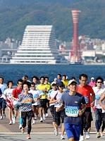 第1回神戸マラソンでポートタワーを背に海岸沿いを走るランナーたち=2011年11月20日