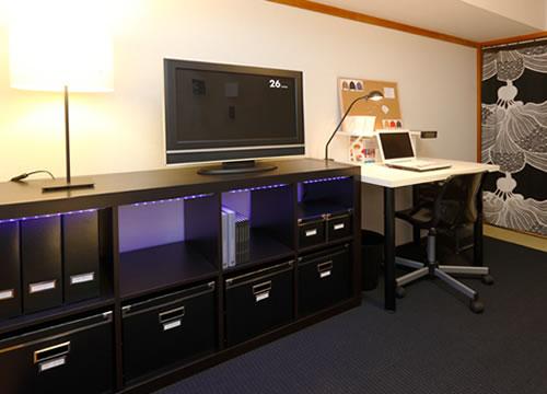 写真:収納兼テレビ台として利用しているのは、横置きしたEXPEDIT(エクスペディート)の書棚。ごちゃごちゃ散らかりがちな小物は、書棚にピッタリ収まるKASSETT(カセット)収納ボックスを活用して、隠す収納を。