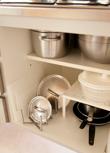 写真:流しの下の収納は、シェルフインサート(RATIONELL VARIERA)などを使って、収納スペースを増やします。鍋やフライパンは、鍋ぶたオーガナイザー(RATIONELL VARIERA)を使って蓋を別にしておくと、出し入れししやすく、省スペースになります。
