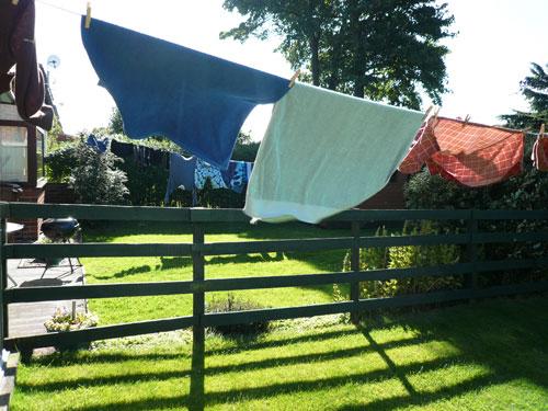 写真:隣家との板塀に沿って翻る洗濯物