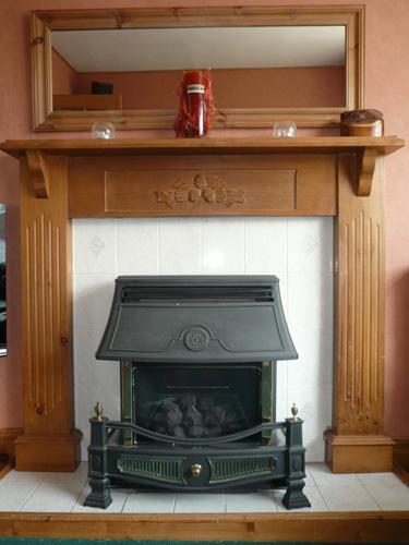 写真:暖炉跡におさまっているガスを燃料とする暖房器具。背後には、家全体を暖房するセントラルヒーティングや給湯用のボイラーが収納されている