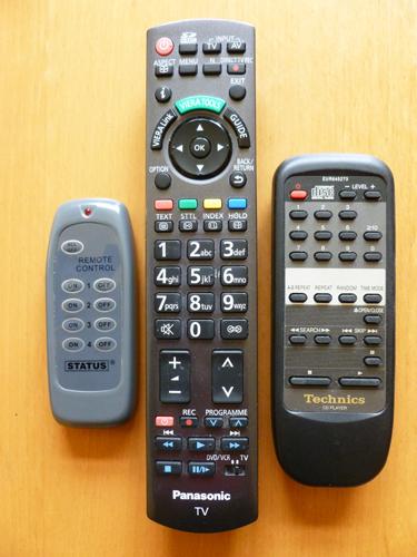 写真:元電源まで切れるリモートコントロール(左)。ボタンは、オンとオフの二つのみ。テレビやステレオ、DVDデッキなど四つの家電に使え、チャンネルやボリューム操作などはそれぞれの家電についてきたリモートコントロールを使用する(中央、右)