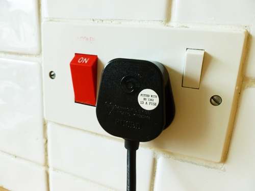 写真:イギリスの一般的なコンセント(右側)。右上にあるのが元電源のスイッチ。左側の赤色のものは、ビルトインガスコンロの点火装置とビルトイン電気オーブンの元電源スイッチ