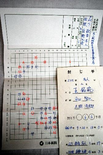 写真:封じ手が記入された棋譜と、その棋譜を入れてあった封筒。羽根挑戦者の封じ手白66は左下「6の十四」のツケ。その部分に赤いボールペンで書かれた○印が見える