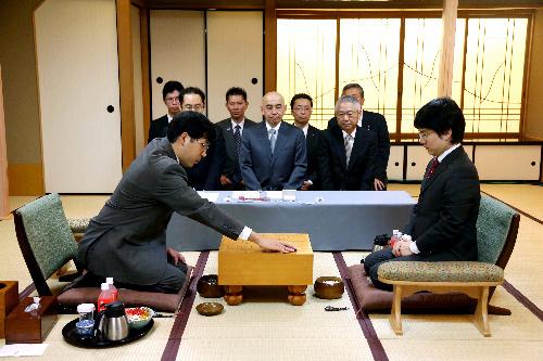写真:第一着を打つ羽根直樹九段(左)。右は山下敬吾名人=27日午前9時、宮崎市、上田幸一撮影
