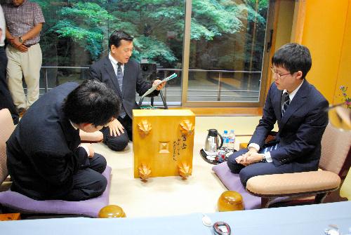 写真:碁盤のいわれを聞きながら、本因坊秀哉の署名をのぞき込む井山裕太名人(右)と山下敬吾本因坊(左)