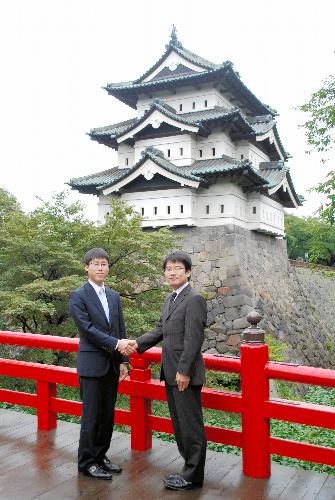 写真:弘前城をバックに握手をする井山裕太名人(左)と挑戦者の山下敬吾本因坊=20日午後3時17分