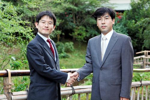 写真:29日の対局室検分後、椿山荘の庭園で握手をする山下敬吾名人(左)と羽根直樹九段