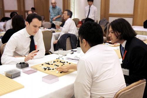 写真:検討室で棋譜を確認するサマースクール参加者たち。奥には、立会人の石田秀芳二十四世本因坊らの姿も。