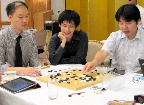 写真:検討室を訪れた張栩棋聖(中)。盤上の勝負の行方を、ほかの棋士らと熱心に検討している