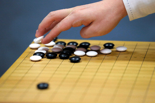 写真:初日の棋譜を並べ直す山下敬吾名人の手=13日午前、甲府市、長島一浩撮影
