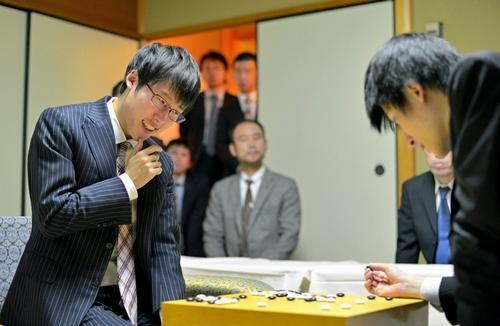 写真:張栩王座(右)を破り、感想戦で笑顔をみせる井山裕太本因坊=22日夜、神戸市中央区、諫山卓弥撮影