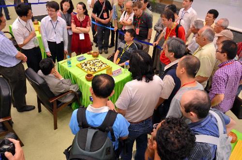 写真:中園清三選手(碁盤の左)の時間が切れ、周囲に人だかりができた=14日、中国広州市、日本棋院提供