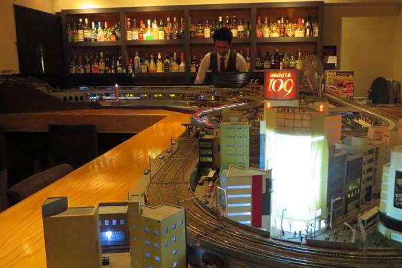 渋谷の街を走り抜ける鉄道模型を眺めながらカクテルを楽しむ