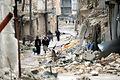 アレッポ東部のハイダリーア地区で砲撃で激しく破壊された建物の間を歩く人々。ガスや食料などの救援物資を受け取って運んでいた=9日午後、アレッポ、矢木隆晴撮影