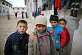 アレッポ東部ジブリーン地区にある、元は倉庫だった建物で避難生活を送る子どもたち。壁には洗濯物が干してあった=9日午後、アレッポ、矢木隆晴撮影