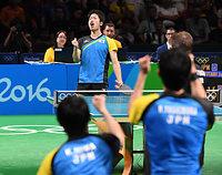 男子団体準決勝の第4試合で、ショットを決めガッツポーズをする水谷隼(奥中央)=竹花徹朗撮影
