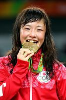 女子48キロ級の表彰式で金メダルをかむポーズを見せる登坂絵莉=17日、カリオカアリーナ、林敏行撮影
