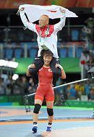 女子48キロ級で金メダルを獲得し、栄和人チームリーダー(上)を肩に担ぐ登坂絵莉=林敏行撮影