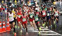 男子マラソンの2キロ付近で、走路の水たまりを踏みながら走る先頭集団=林敏行撮影