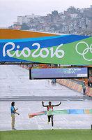 カーニバルの会場「サンボドロ」に設けられたゴールのテープを切る、男子マラソンで優勝したキプチョゲ=長島一浩撮影