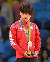 女子48キロ級で3位となり、銅メダルを見つめる近藤亜美=竹花徹朗撮影