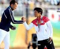 スラローム男子カナディアンシングルの表彰式で、優勝したフランスの選手(左)と握手する3位の羽根田卓也=林敏行撮影
