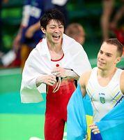 男子個人総合で金メダル獲得を決めて喜ぶ内村航平(左)=林敏行撮影
