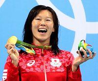 女子200メートル平泳ぎの表彰式で、金メダルを掲げ笑顔を見せる金藤理絵=11日、五輪水泳競技場、西畑志朗撮影