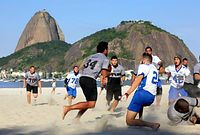 ボタフォゴ海岸でアメリカンフットボールの試合をする、地元クラブチームの選手たち