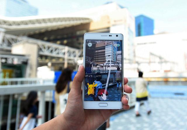 配信が開始された「Pokémon GO」(ポケモン ゴー)。JR大阪駅前にもピカチュウが現れた=2016年7月22日、大阪市北区
