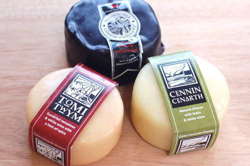 写真:購入したチーズ。ワックスで覆われているので、そのままで約6カ月の保存が可能。黒いのがチェダーチーズ。手前の二つはそれぞれ、サンドライドトマトと、リーク(ポロ葱)と白ワインが入っていて、クリーミーでこくがあり、どれもワインがすすむ