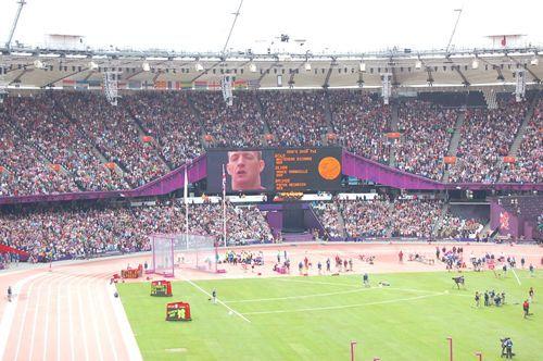 写真:メダル授賞式でスクリーンに大写しされる英国選手、リチャード・ホワイトヘッドさん