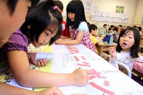 写真:選手一人一人にメッセージを書き込むロンドン日本人学校の児童たち=矢木隆晴撮影