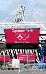 写真: ロンドン五輪開幕まで2週間となった13日、ロンドン東部に新設された五輪公園内では、本番に向け各施設で最終工事が続いていた。メーンスタジアム間近のゲートでは、五輪マークも掲げられ、入場客を待つばかりとなっていた。