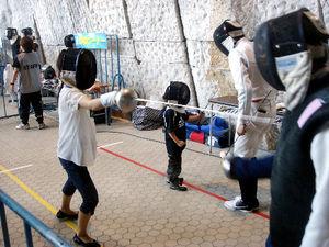 写真:指導員に教えられながら、フェンシングを体験する子どもたち=東京・代々木競技場